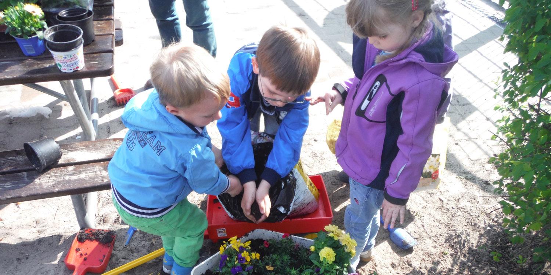 Kinder schütten Erde aus einem Sack in einem Blumentopf