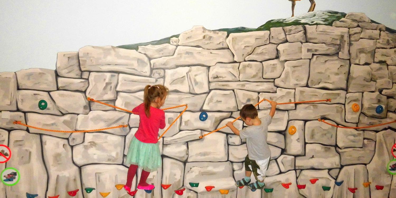 Zwei Kinder klettern an einer kleinen Kletterwand