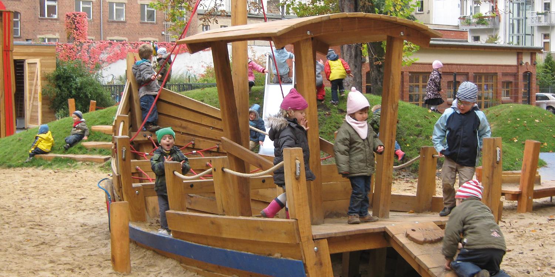 Viele Kinder spielen auf einem Spielplatz und sind auf einem Holzgerüst, das aussieht wie ein Boot