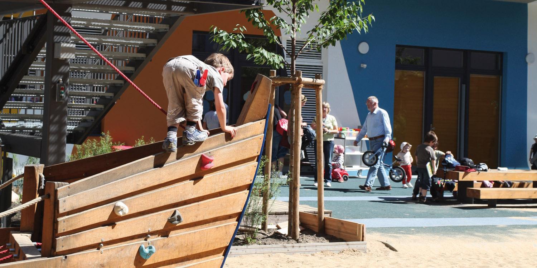 Im Vordergrund sieht man einen Jungen, der auf einem Klettergerüst klettert und im Hintergrund sieht man Eltern und Kinder und die Fassade der Kita