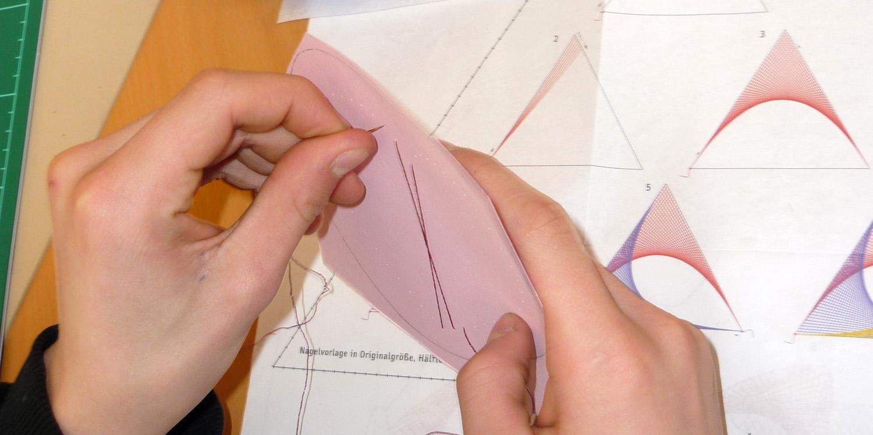 Zwei Hände und eine Vorlage. Die linke Hand hält eine Nadel mit Faden und die rechte Hand ein Stück Pappe mit einer Vorlage.