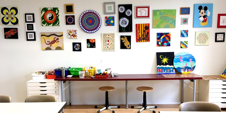 Eine Wand mit gestickten Bildern und darunter befindet sich ein Tisch mit dem benötigten Werkzeug zum Sticken
