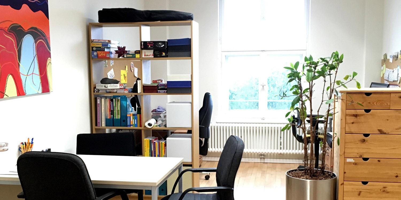 Ein Raum mit zwei Regalen, einem Tisch und vier Stühle und eine Pflanze