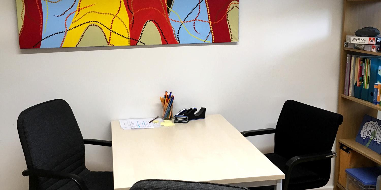 Ein Tisch mit drei Stühlen und Schreibutensilien