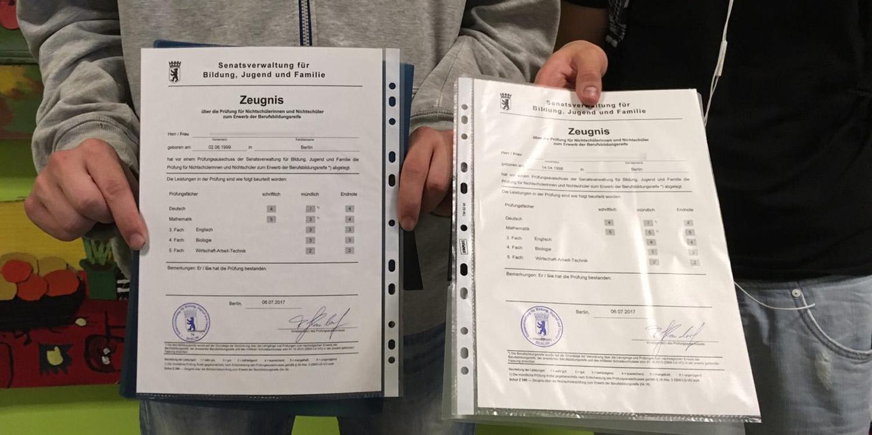 Zwei Schüler zeigen ihre Zeugnisse