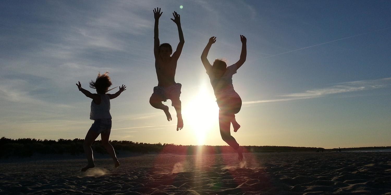 Drei junge Menschen springen am Strand bei einem Sonnenuntergang in die Luft.