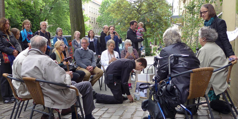 Menschen stehen und sitzen vor einer knienden Person