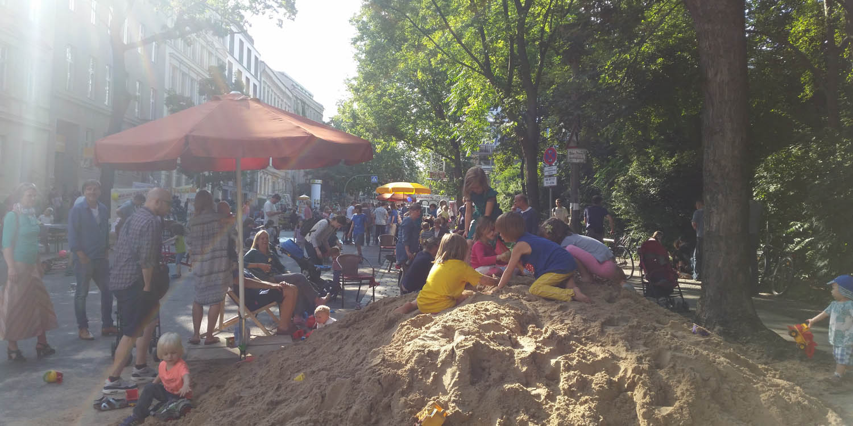 Im Hintergrund sieht man ein Fest und im Vordergrund ist ein Sandhaufen, wo Kinder spielen