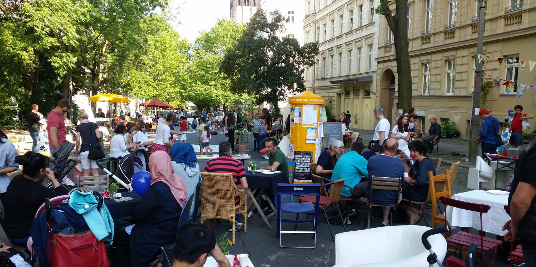 Viele Leute, die auf einem Straßenfest sitzen