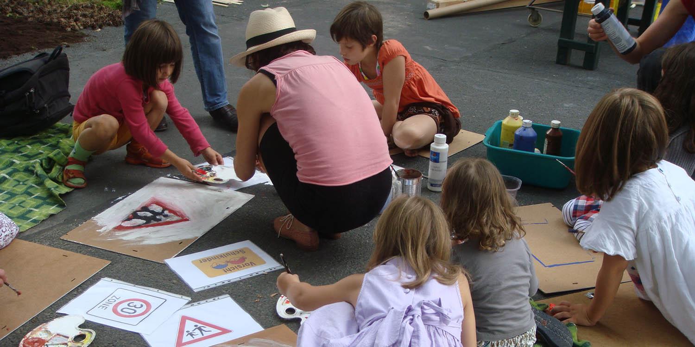 Kinder malen Straßenschilder auf Pappe