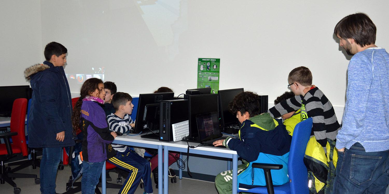 Kinder an Laptops und Rechnern unter Aufsicht eines Erwachsenen