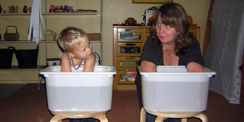 Kleiner Junge und Erzieherin halten ihre Hände in jeweils ein Becken mit Wasser.