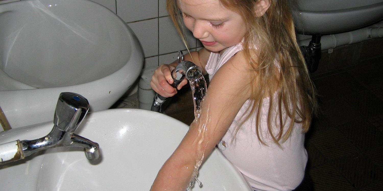 Mädchen wäscht sich mit einem Schlauch an einem Waschbecken den Arm