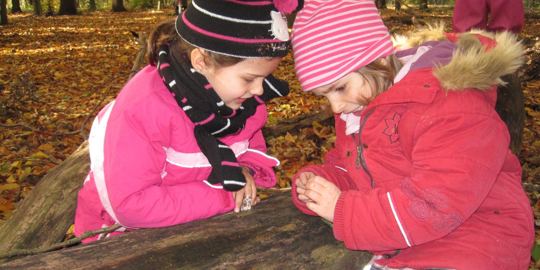 Zwei Mädchen schauen auf die Hände von einem der beiden Mädchen, da das Mädchen irgendetwas in der Hand hält