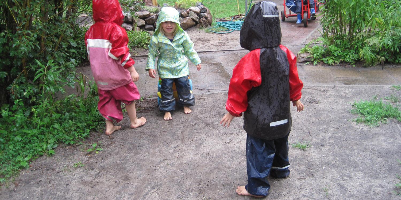 Drei kleine Kinder laufen Barfuß und in Regenkleidung auf leicht feuchter Erde