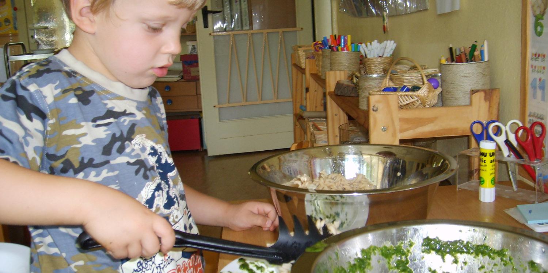 Kind macht sich Nudeln auf einen Teller