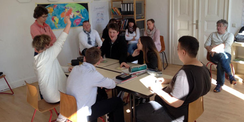 Eine kleine Gruppe Schüler sitzen zusammen an mehreren kleinen Tischen mit Schulmaterialien. Hinter den Schülern sitzen mehrere Erwachsene und eine Frau steht bei den Schülern.