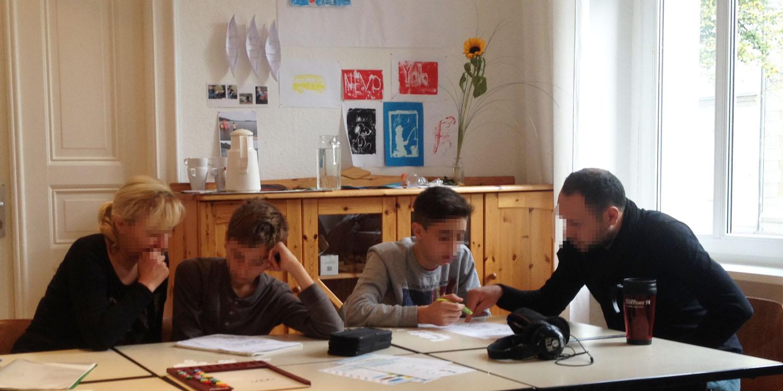 Zwei Schüler sitzen mit jeweils einem Erwachsenen zusammen und besprechen etwas auf einem Blatt Papier