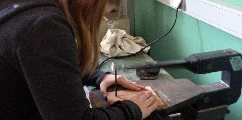 Eine weibliche Person sägt etwas von einem Holzbrett ab.