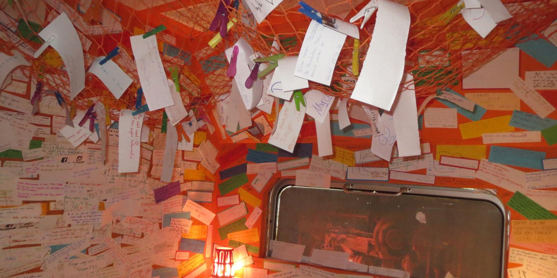 Zettel mit Wünschen und Eindrücken an die Wände und die Decke eines Raumes geklebt