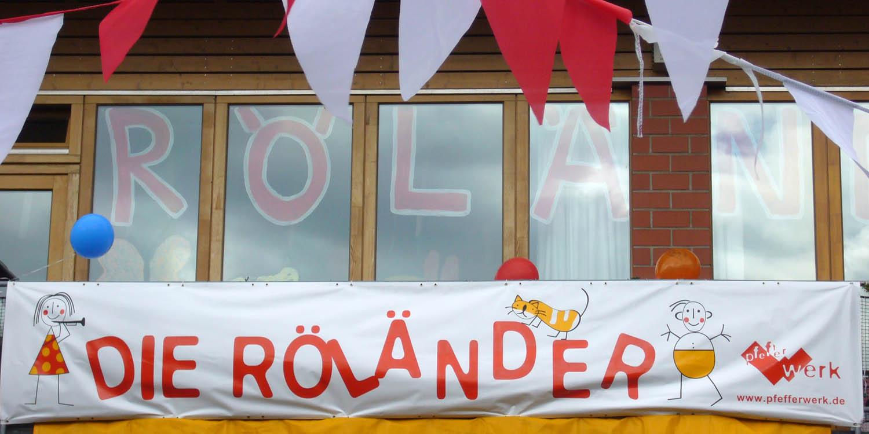"""Hausfassade mit einem Banner, auf dem """"Die Röländer"""" steht."""