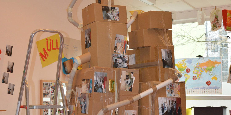 Zwei Skulpturen aus Kartons und Papprollen auf den Fotos von Kindern aus der Kita sind.