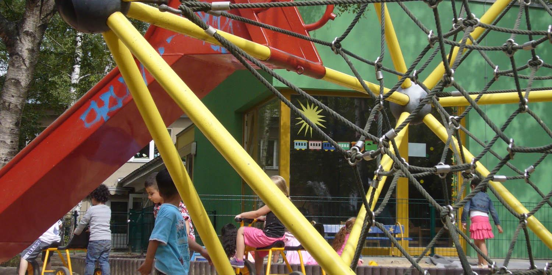 Klettergerüst mit Rutsche und im Hintergrund spielen Kinder