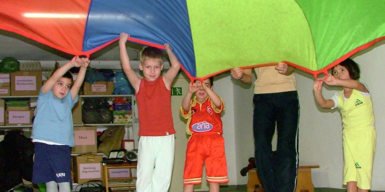 Mehrere Kinder die mit einem Fallschirm spielen