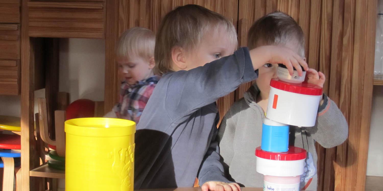 Zwei Kinder bauen einen Turm aus Behältern