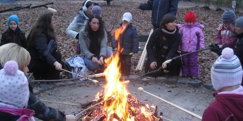 Eltern und Kinder beim Stockbrot grillen am Lagerfeuer
