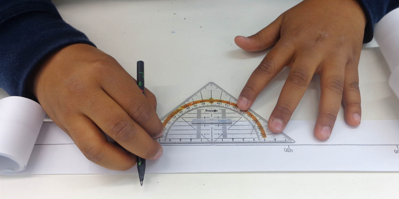 Zwei Hände zeichnen mit Hilfe eines Geodreicks eine gerade Linie auf einem Blatt Papier.