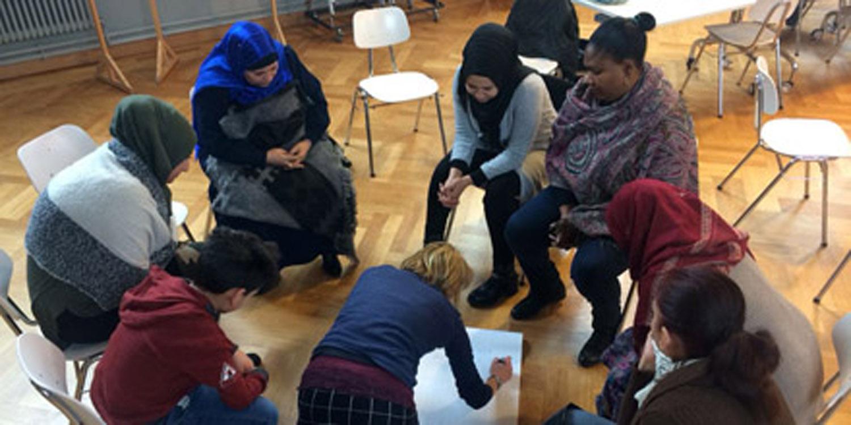 Schülerinnen und Schüler sitzen in einem Kreis und beschreiben Plakate.