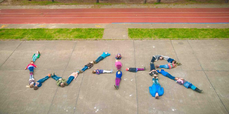 Mehrere Schüler liegen auf dem Boden und formen mit ihren Körpern W-I-R