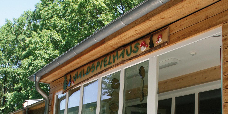 """Hausfassade mit einem Holzbrett, auf dem """"Waldspielhaus"""" steht."""