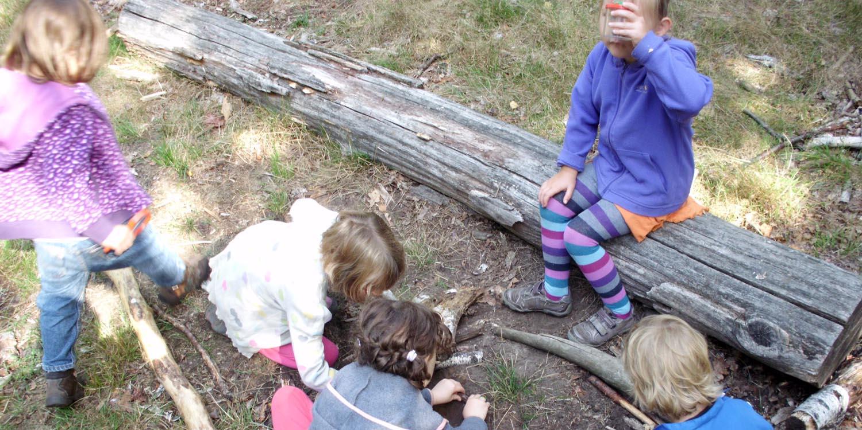 Kinder beobachten draußen etwas auf dem Boden