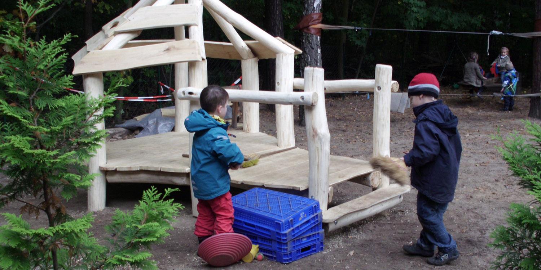 Zwei Kinder stehen vor einer kleinen Holzhütte und haben etwas in der Hand