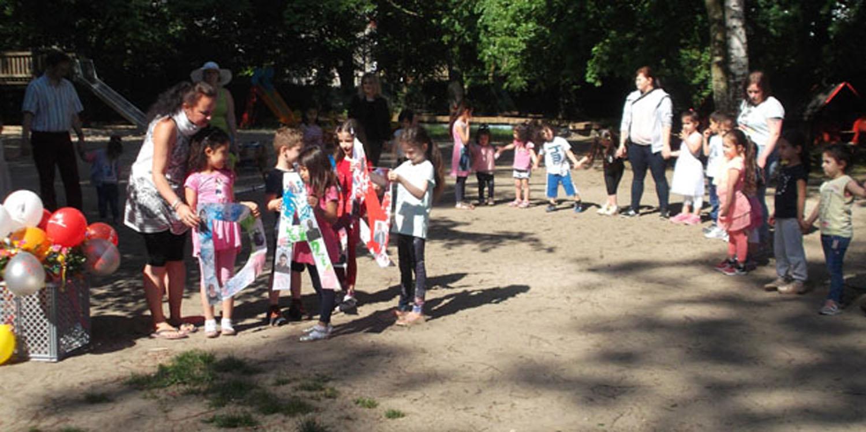 Kinder und Erwachsene, die draußen in einem Halbkreis stehen und fünf Kinder, die drei Buchstaben halten.