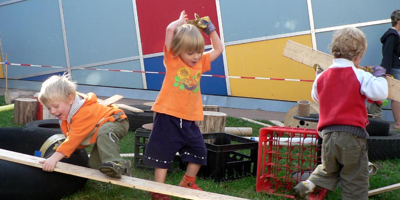 Kinder die auf Holzbrettern klettern und wegtragen und einige Getränkekästen und Reifen liegen verteilt aufm dem Boden.
