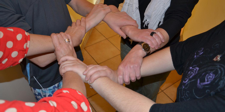 Vier Menschen haben die Hände ineinander verhakelt und stellen eine Verbindung her, die Unterstützung symbolisiert.