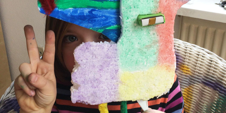 Eine selbstgebastelte Maske, hinter der Maske schaut ein Mädchen durch