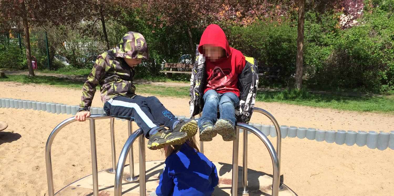 Drei Kinder sind auf einem Drehkarussel
