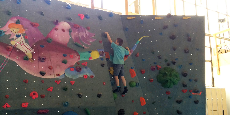 Ein Junge klettert auf einer Kletterwand