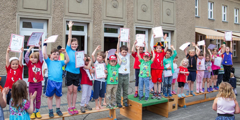 Viele Kinder, die draußen auf Sportbänken stehen und eine Urkunde hoch halten und eine Medaille um den Hals haben