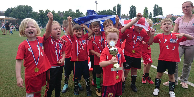 Eine Fußballmannschaft der Kita, die Haben Medaillien um den Hals und einer trägt einen Pokal. Die Kinder tragen auf ihren Trikots eine Flagge der USA und heben die Nationalflagge der USA über sich