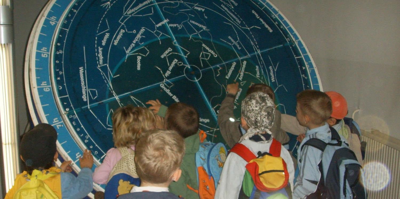 Kinder stehen vor einer großen blauen Scheibe mit dem Sternenhimmel.