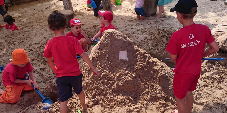 Ein Sandkasten in dem Kinder einen Berg aus Sand aufschaufeln