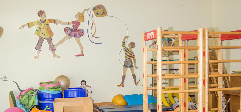 Sportgeräte und an der Wand sind drei Figuren, zwei davon tanzen miteinander und die andere Person lässt einen Drachen steigen