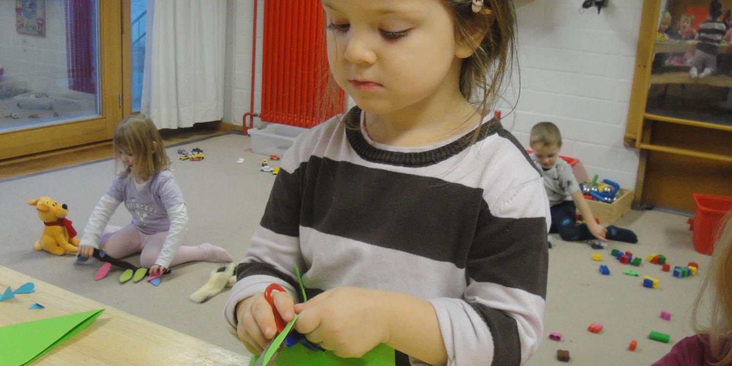 Ein Mädchen bastelt etwas und im Hintergrund sieht man zwei Kinder spielen