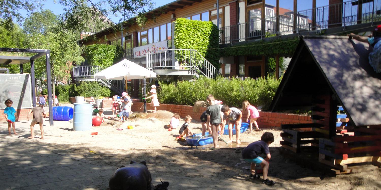 Viele Kinder die auf dem Sandspielplatz der Kita spielen