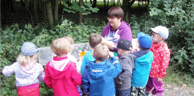 Mehrere Kinder, die vor einer Holzbank stehen und mit einer erwachsenen Person etwas trinken